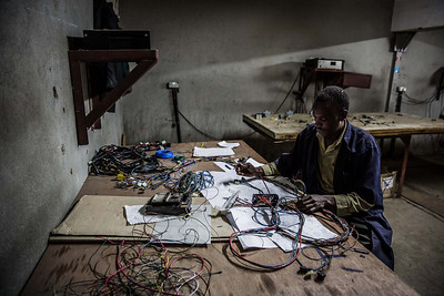 A worker checks the wires with the electrical engineer's diagram in an automobile wiring factory in Nairobi, Kenya.