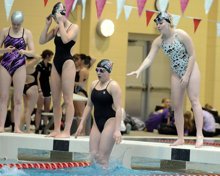 Loveland Delaney McNally gets in the pool for warmups with a little help from teammate Ella Doerr at Saturday's Front Range League Championships at the Veterans Memorial Aquatic Center. (Mike Brohard/Loveland Reporter-Herald)