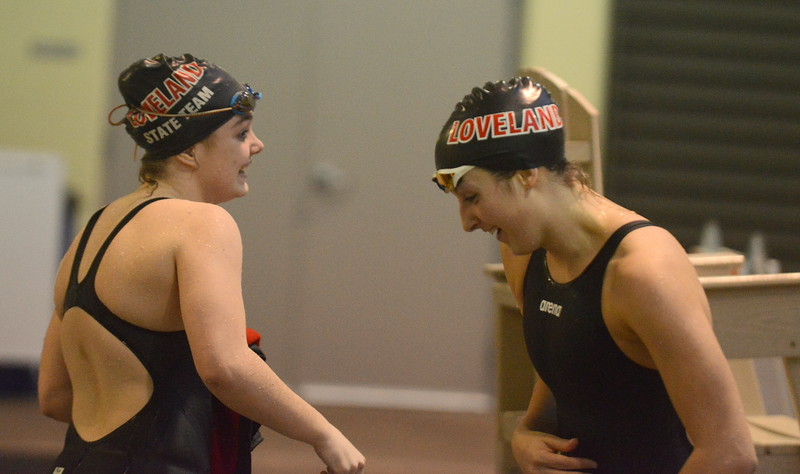Loveland's Ella Doerr (left) and Jordan Keck congratulate each other on hitting the 4A state-qualifying time in the 50-yard freestyle at Friday's preliminary session of the Front Range League Championships. In a tough field, neither of them made it back for finals, nor did teammate Shannon Tyler, who also hit the time. (Mike Brohard/Loveland Reporter-Herald)