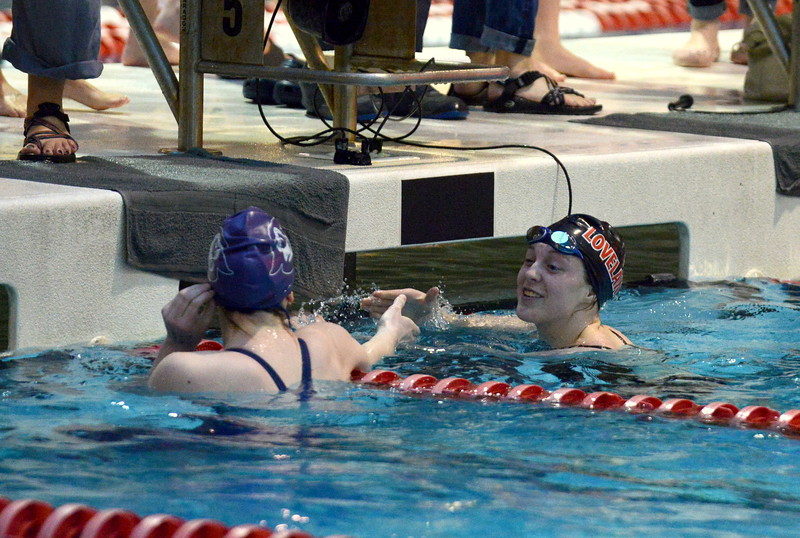 Loveland's Shannon Tyler (right) shakes hands with Fort Collins' Riley Harrison after finishing the 50-yard freestyle at Friday's preliminary session of the Front Range League Championships. Tyler hit the state cut in the event with a 26.25. (Mike Brohard/Loveland Reporter-Herald)