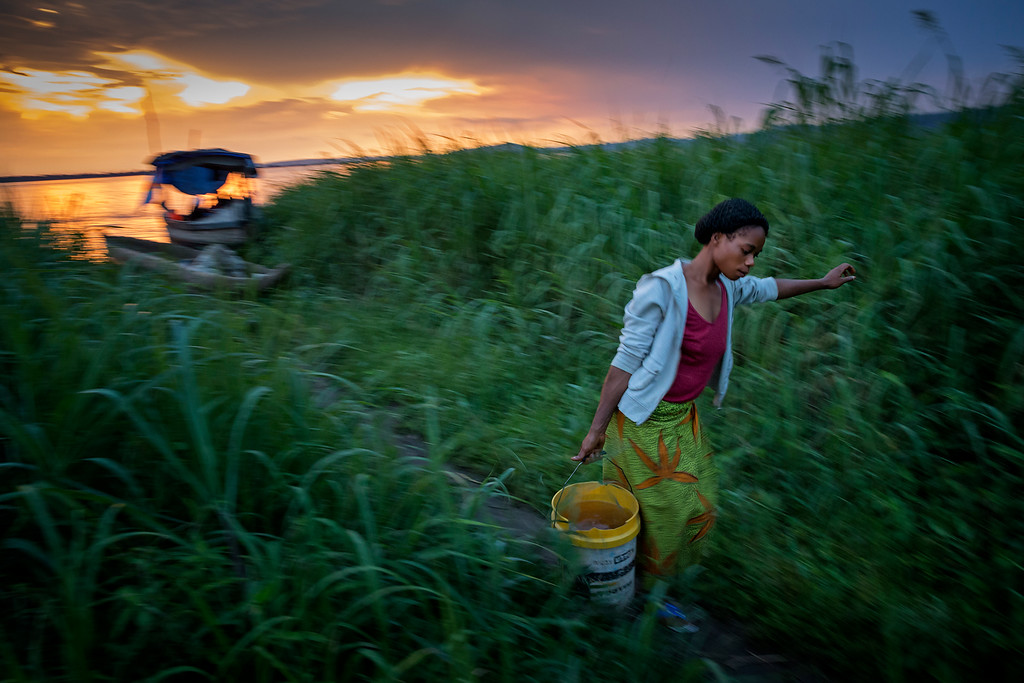 A woman living in the swamps just outside Kinshasa picks up water from Congo River to use for making food.