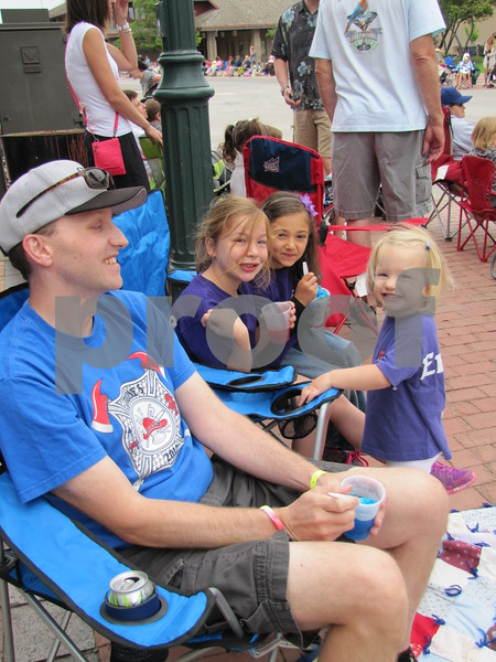 Ryan Brown, Joscelyn Kahler, Olivia Daniel, and Clara Brown (standing) enjoy slushes while waiting for the parade to begin.