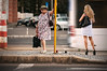 Journey of Waiting | Street Photography Two Women Waiting for the Bus at a Bus Stop in Bucharest Romania Contrast of Generations Young and Older People Colorful Street Fashion Clothes Short Shorter Skirt