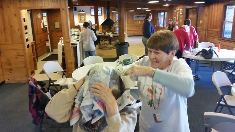 Janice Sivard helps tape Barbara Vance's hat