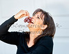 Attractive Woman holding Grapes to her Mouth