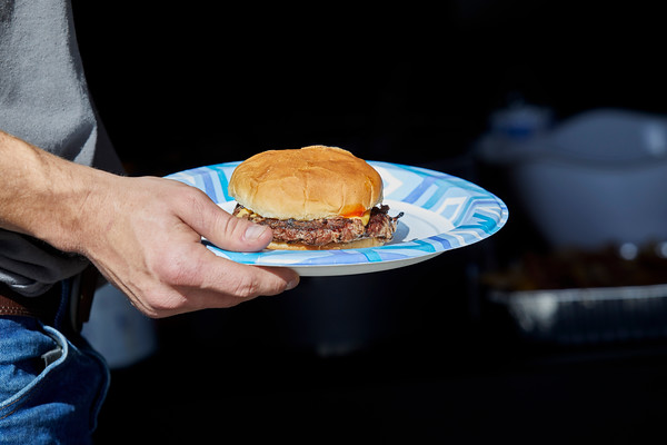 Hand holding a paper plate with a Hamburger on it