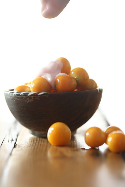 Wooden bowl with Cape gooseberries with yoghurt
