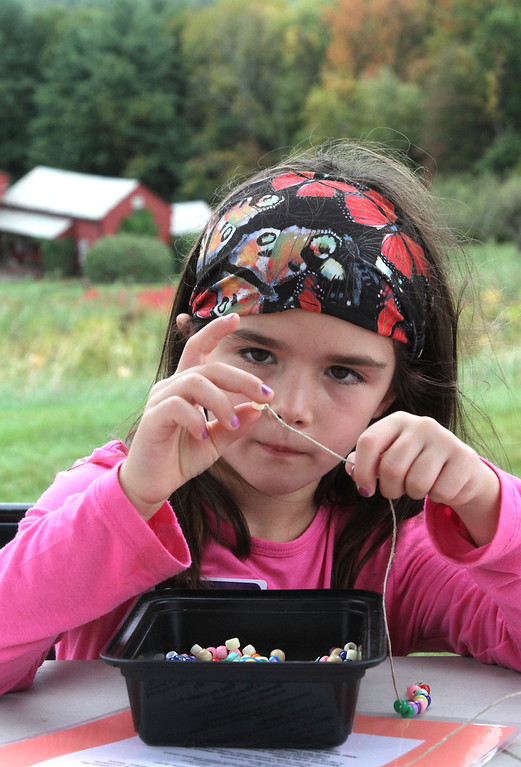 . Victoria Januskiewicz, 6, of Groton, strings beads for her doll, at the Fruitlands Harvest Festival in Harvard. Nashoba Valley Voice Photo by David H. Brow
