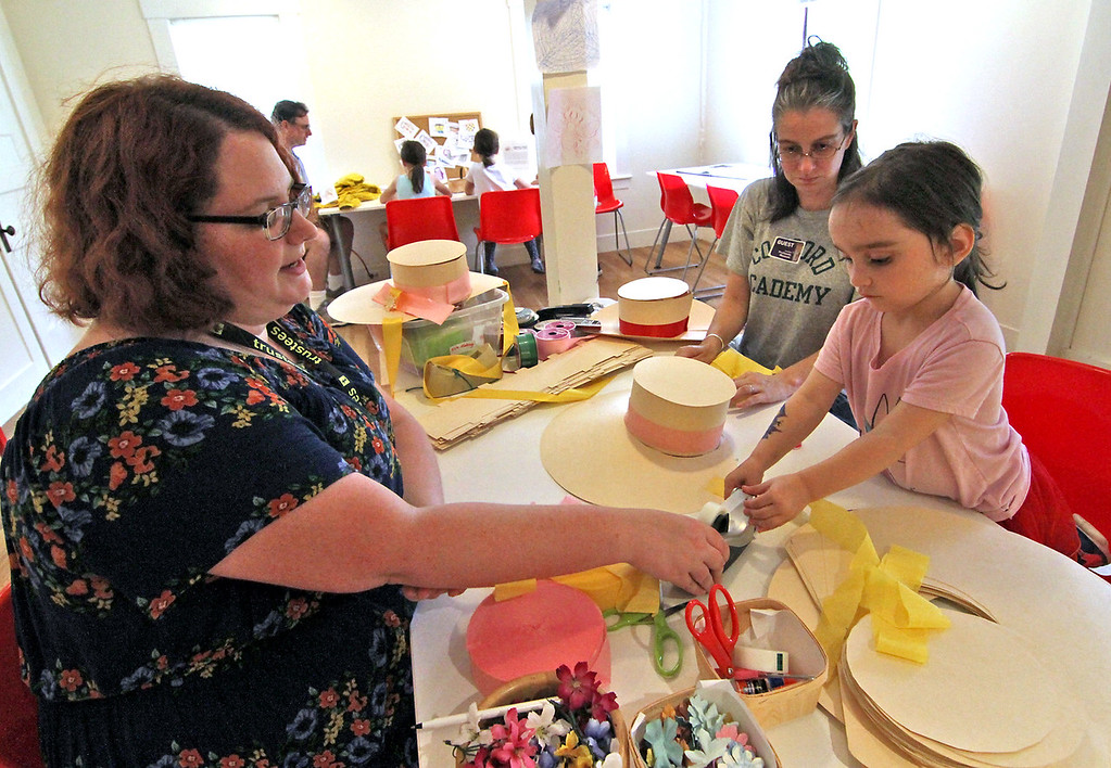 . Making old time bonnets at the Fruitlands Harvest Festival is L-R, staff worker Kayla Bishop of Groton, Michelle Worth of Acton and her daughter Charlotte Worth, 4. Nashoba Valley Voice Photo by David H. Brow
