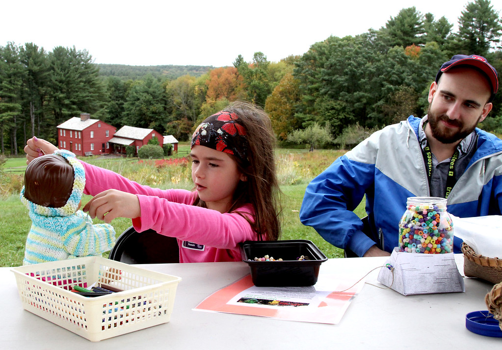 . Victoria Januskiewicz, 6, of Groton, trys out a necklace on her doll Autum, as Fruitlands staff worker Mark Gozzo looks on at crafts table for the Fruitlands Harvest Festival in Harvard. Nashoba Valley Voice Photo by David H. Brow