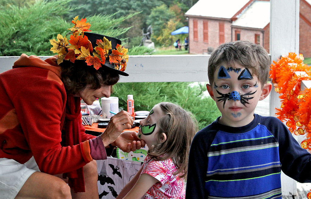 . Renee de la Sea, of Ipswich and Sea Peas Face Painting, paints a face on Ada-June Snow,7, after her brother Damian Snow,5, had his face painted at the Fruitlands Harvest Festival in Harvard. Nashoba Valley Voice Photo by David H. Brow