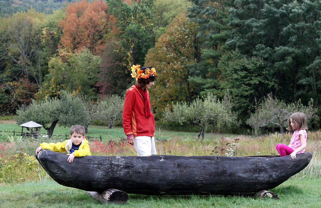 . Renee de la Sea, with Sea Peas Face Painting of Ipswich, watches over, Damian Snow, 5, and his sister Ada-June Snow, 7 of Lunenburg, as they try out a  Native American dug-out canoe at the Fruitlands Harvest Festival. Nashoba Valley Voice Photo by David H. Brow