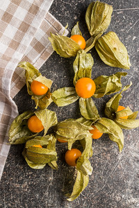 Physalis peruviana fruit on old kitchen table. Top view.