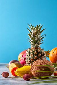 Creative layout made of fruits pineapple, orange, lime, pitaya, carambola, coconut, mango, kumquat w