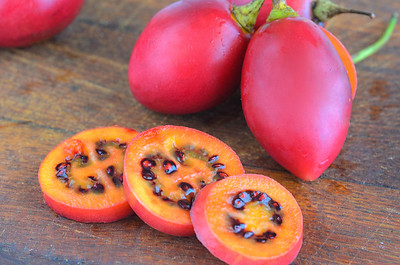 Red Tamarillo  Or  Tree Tomato Cut Into Slices On Cut Board. Exotic Fruit Tamarillo Background With