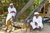 Arab men in traditional dress demonstrate the use of water buffalo to draw water from a desert well in Fujairah, UAE.
