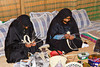 Muslim women in traditional dress demonstrate their activities in the home at the Heritage Center in Fujairah, UAE.