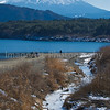 A man walks on the beach at a lake near Mt. Fuji Fuji Five Lakes, Yamanashi Prefecture, Japan