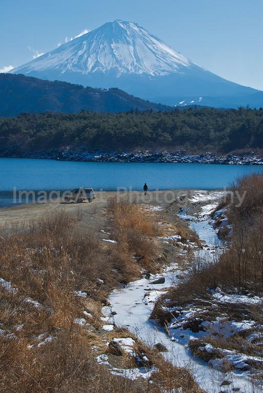 A man walks on the beach at a lake near Mt. Fuji Fuji Five Lakes, Yamanashi Prefecture, Japan