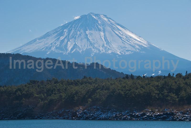Mount Fuji behind tree covered hills Fuji Five Lakes, Yamanashi Prefecture, Japan