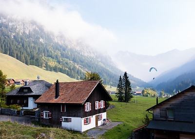 A paraglider coming down in front of a stunning scenery