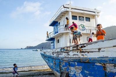 Kids playing on fishing boat, Kuta, Lombok