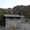 This outhouse is in a campground on the road between Cody and Yellowstone in Wyoming; it travels along the North Fork of the Shoshone River, with its green trees near the river and rugged canyon walls above.  May 14th, 2014