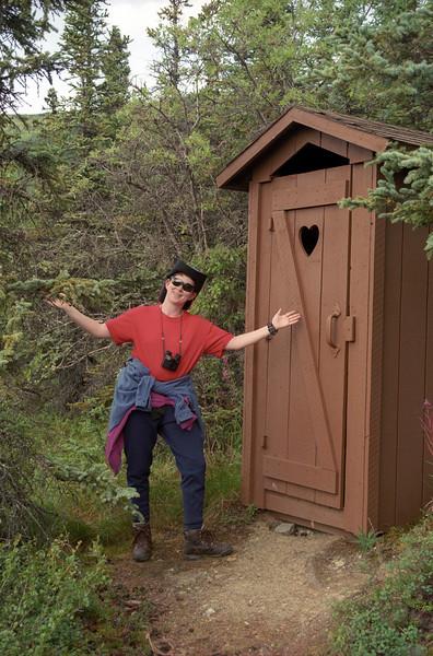Patti presents the latrine outside our cabin at Camp Denali, Denali National Park, Alaska. August 2000