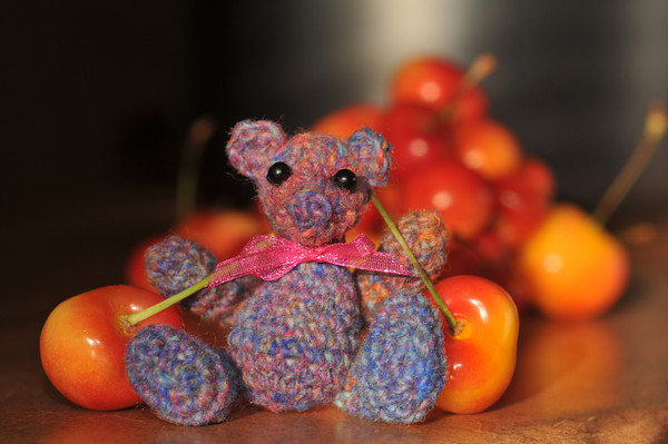 Noro sock leftovers bear with Rainier cherries...<br /> because this little guy was hungrier than me!