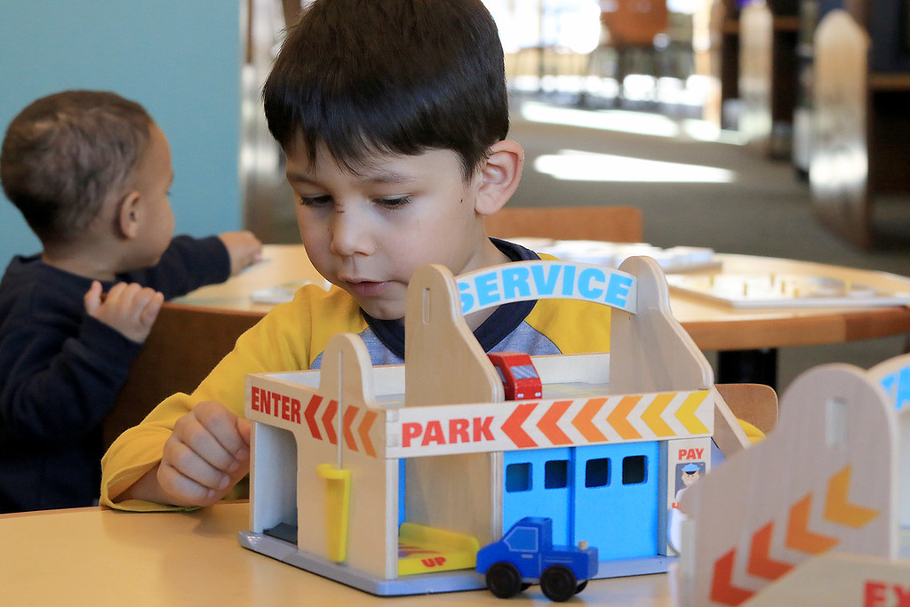 . The Leominster Public Library childrens room is always a great place for kids to come and Learn, play and have fun. David Pantigoso, 6, enjoys playing with the wooden toy service station set they have in the Children\'s room on Thursday, January 3, 2019. He and his family are home visiting family in the area. He lives with his family in Cusco, Peru. SENTINEL & ENTERPRISE/JOHN LOVE