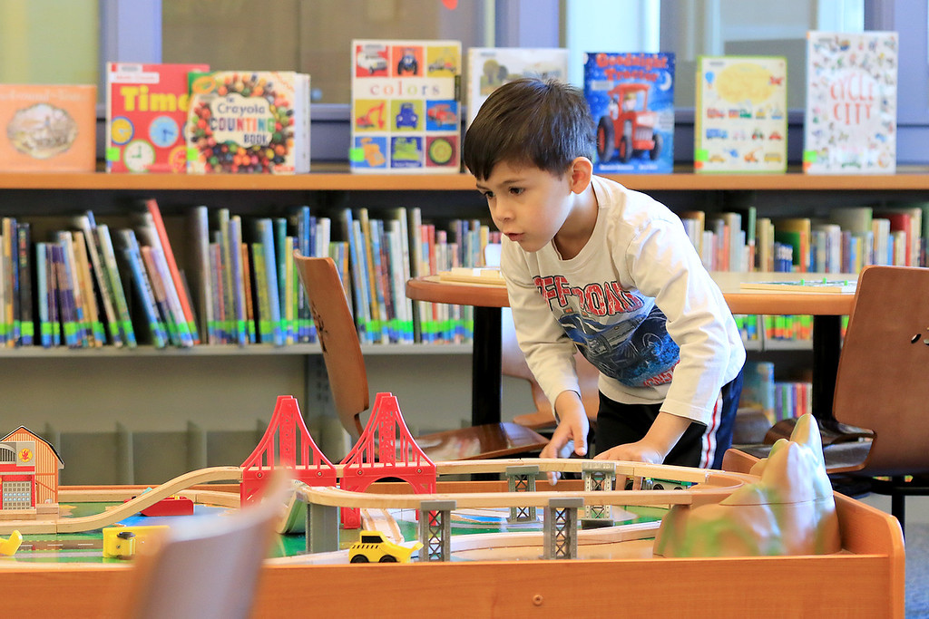 . The Leominster Public Library childrens room is always a great place for kids to come and Learn, play and have fun. Andrew Pantigoso, 4, enjoys playing with the wooden toy train set they have in the Children\'s room on Thursday, January 3, 2019. He and his family are home visiting family in the area. He lives with his family in Cusco, Peru. SENTINEL & ENTERPRISE/JOHN LOVE