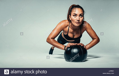 horizontal-shot-of-young-fit-woman-doing-push-up-on-medicine-ball-JJPB01