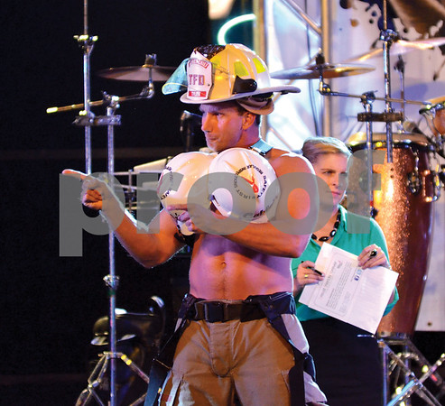 A firefighter confidently displays a bra made of hard hats. (Victor Texcucano)