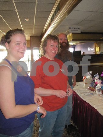 "Tristin Nelson, and Julie and Matt Harrold look over some items on the silent auction table at ""A Concert to Remember"" fundraiser for Alzheimer's held at the Best Western Starlite."