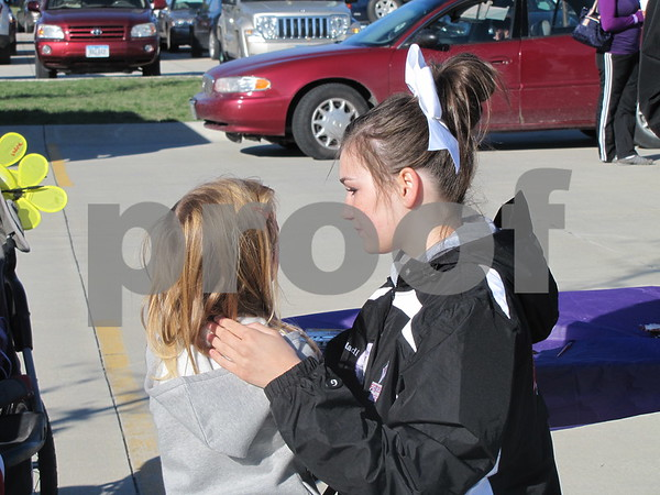 Fort Dodge Senior High cheerleader Maddie Goodner applies face paint to Aleah Lovain.  The FDSH cheerleaders were volunteering at Alzheimer's Walk.