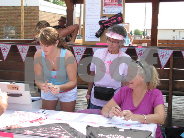 Courtney Thrams, Deb Schuh, and Dawn Thrams sell T-shirts and scarves before the 'Angel Ride' begins.  The fundraiser was held at the Community Pizza in Fort Dodge.