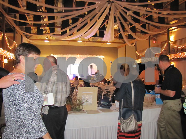Attendees look over the silent auction items before dinner at the fundraiser for LifeWorks.