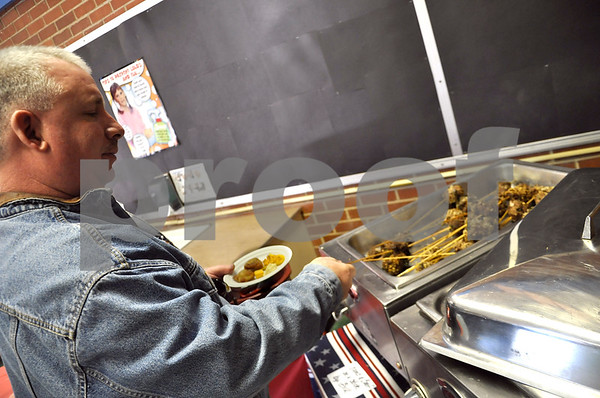 -Messenger photo by Joe Sutter<br /> <br /> Ken Ewing picks up some Lamb and Beef on a stick at the AFES Inauguration Bash. A variety of unusual foods were available on the buffet line, including New Orleansean blackberry chicken, homemade wontons and stuffed peppers.