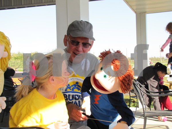 Doug Brightman entertains one of the children at the event with his puppet.