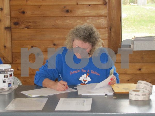 "Liz Rusher, organizer of the Polar Plunge at Badger Lake works to gets everyone registered before the 'Plunge'.  Rusher also took a dip in the chilly waters as part of team ""Pete the Cat""."