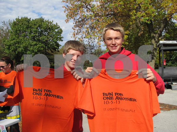 Luke Jacobson and Austin Hintch show off their shirts after signing up for the 5K.