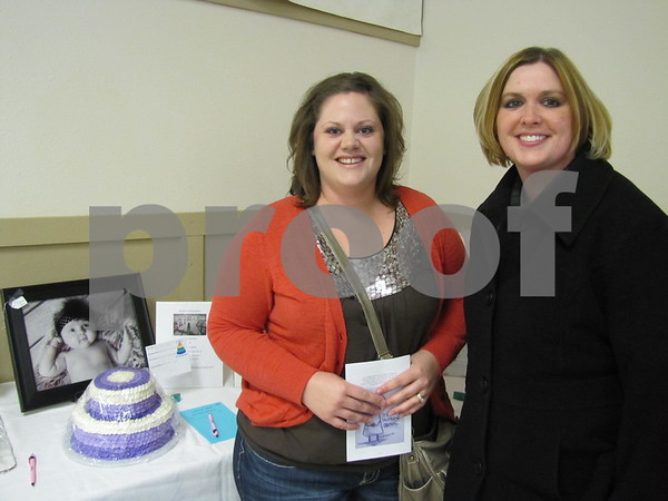 Nicole Scharn and Jana Bartlett standing next to the cake Scharn created, and the photograph by Bartlett.