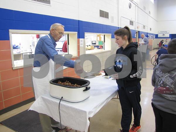 Floyd Herum serves Mara Crimmins at the breakfast fundraiser.