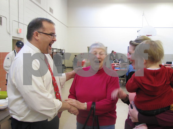 Jim Seward, Director of Youth Shelter Care, shared a laugh with Lois Dencklau at the YSC Omelet Breakfast with Santa fundraiser.  Amy and Lyla Seward are on the right.