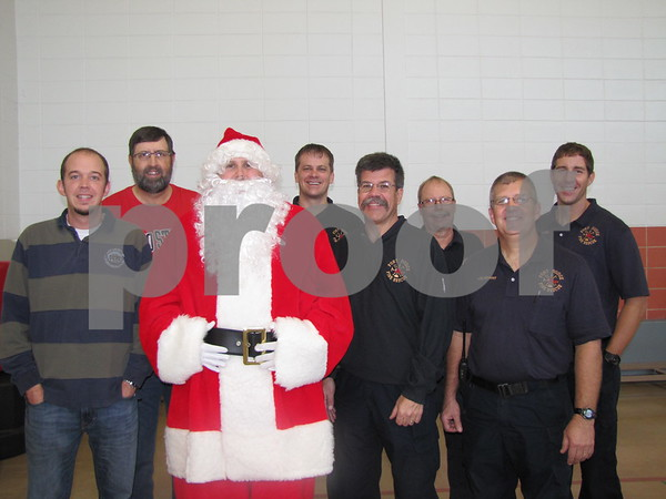 Santa posed with Aaron Will of Youth Shelter Care, Bob Marzean of Cargill, and members of the Fort Dodge Fire Department.  The fire fighters had come for breakfast to support YSC.