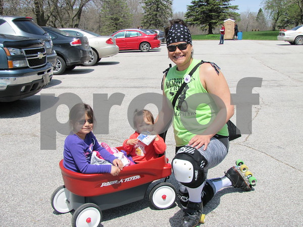 "Katie Taukei, ""PounderHer-Down"", of the Dakota City Demolition Crew, with her children Olivia and Beyla Debevec. Taukei was 'rolling' with her roller blade team to help raise money for the Opportunity Village."