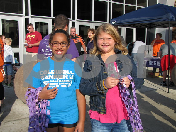 Young volunteers McKierra Harvey and Ashlyn Headlee handed out purple chain necklaces to participants at the Walk for Alzheimers.