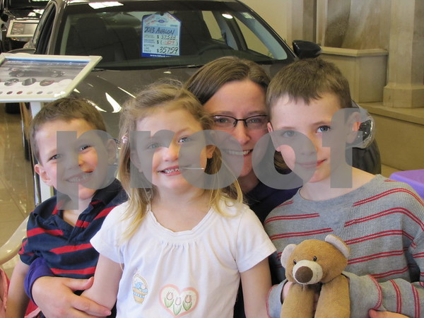 Mindy Waychoff and her children, Dalton, Libby, and Caden are all smiles after filling up on wings at the Relay For Life fundraiser held at Fort Dodge Ford.