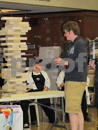 An attendee tries his hand at the giant Jenga game at the Sneakers booth.