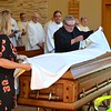 June Rios, one of Fr. Joe's caregivers, and Br. Brian Tompkins, cover the casket with the pall